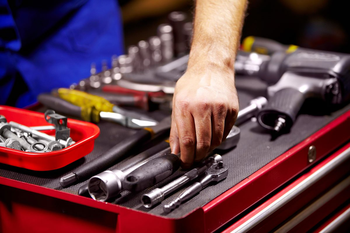 man's hands grabbing a tool from his toolbox