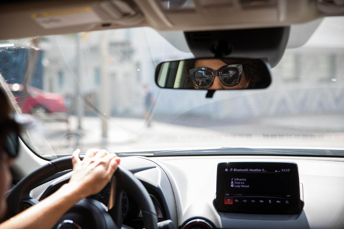 woman looking through rearview mirror in car
