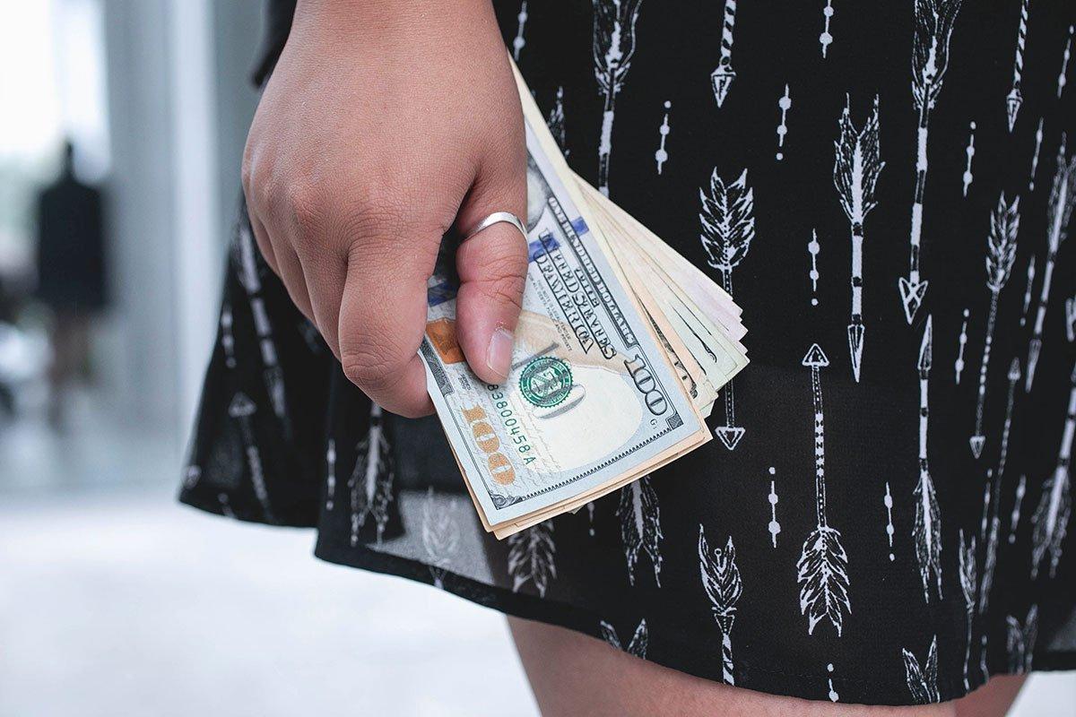 A woman's hand holding U.S. money