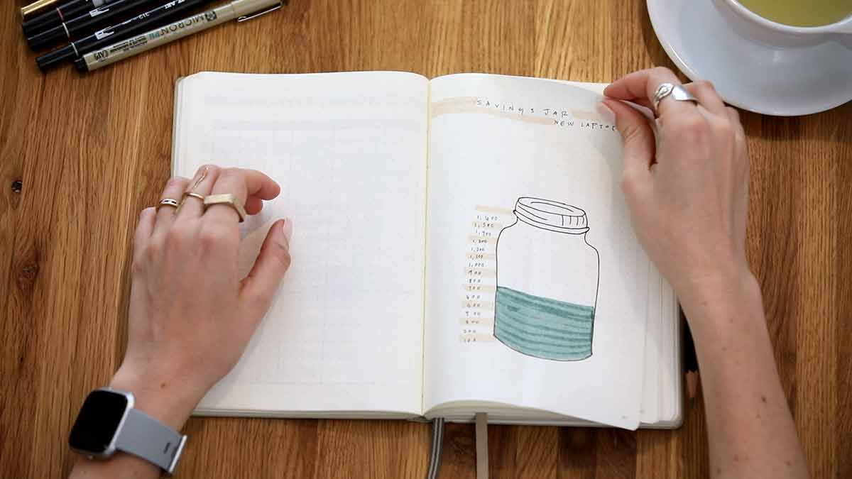 A hand-drawn jar that is partially shaded in is used to track a savings goal.