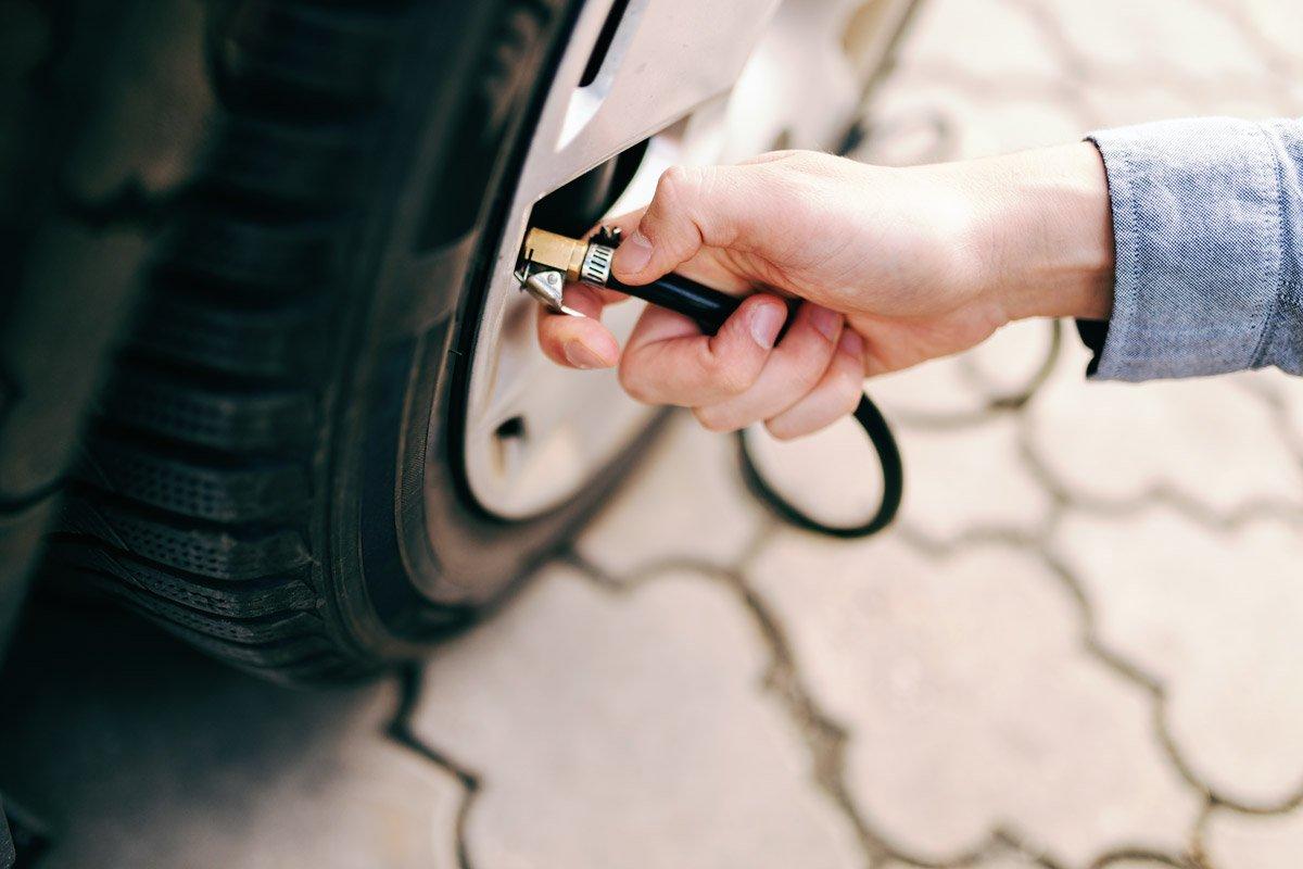 A person checks there tire pressure.