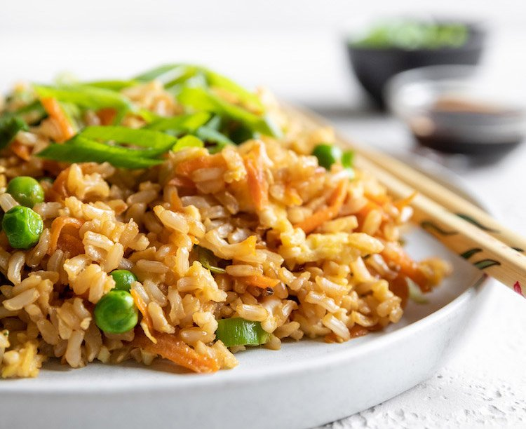 Healthy fried rice is shown in this photograph on a while plate with chopsticks.