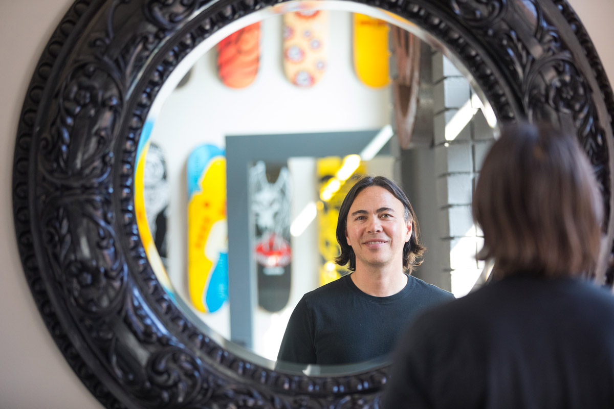 A man poses for a portrait in front of a mirror.