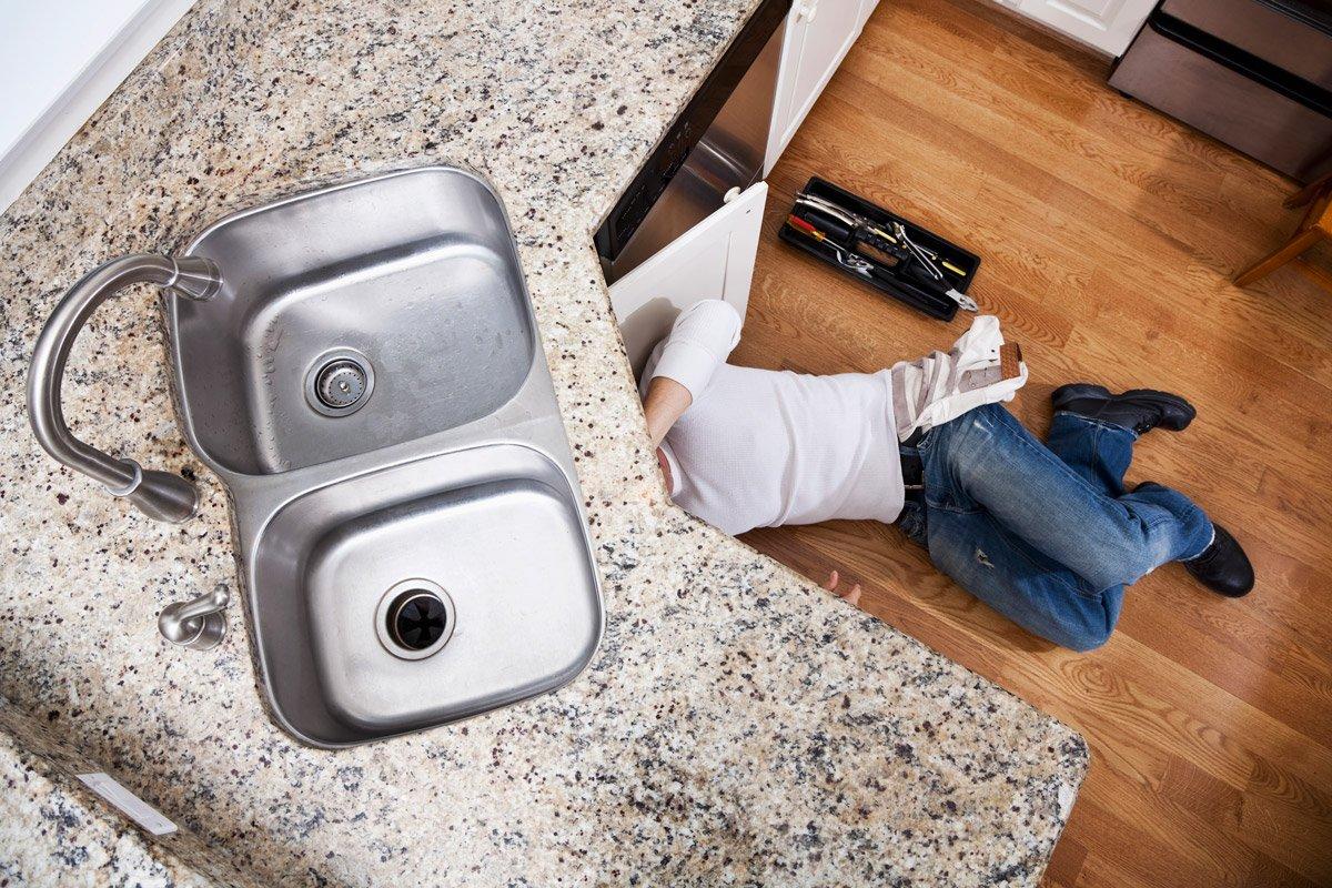 A plumber fixes underneath a kitchen sink