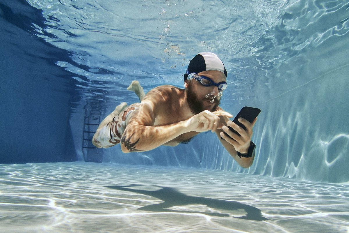 A man types on his phone underwater.