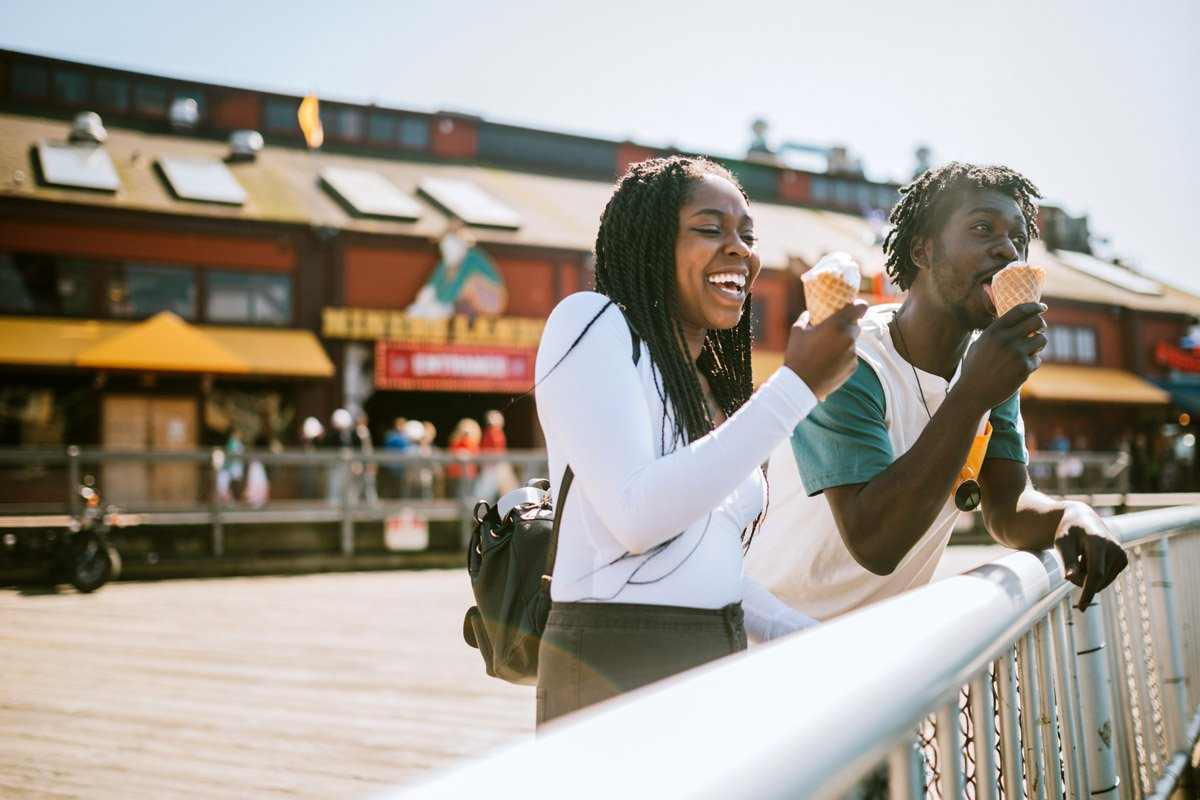 A couple eat ice cream on a pier in Seattle.