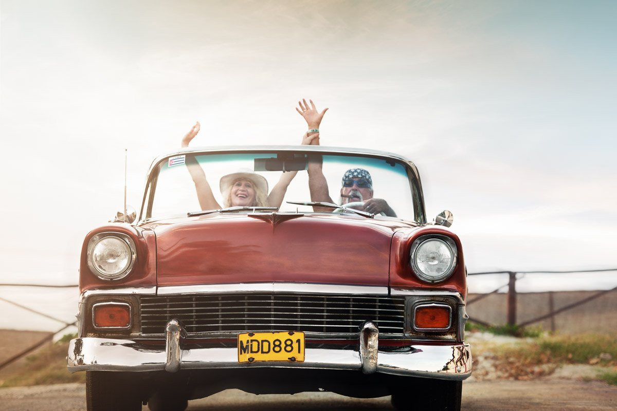 A couple look excited as they drive in an old red convertible.