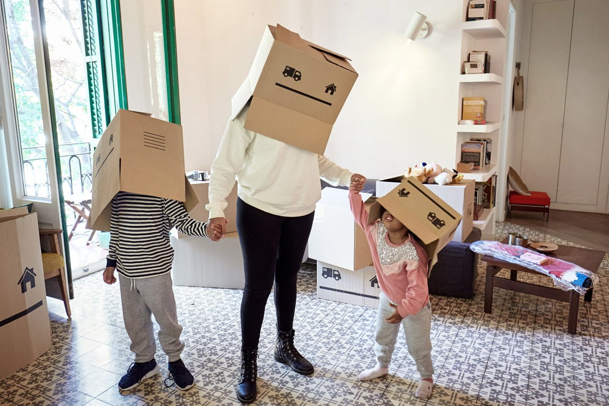 A mom plays with her children as they put boxes over their heads while being silly.
