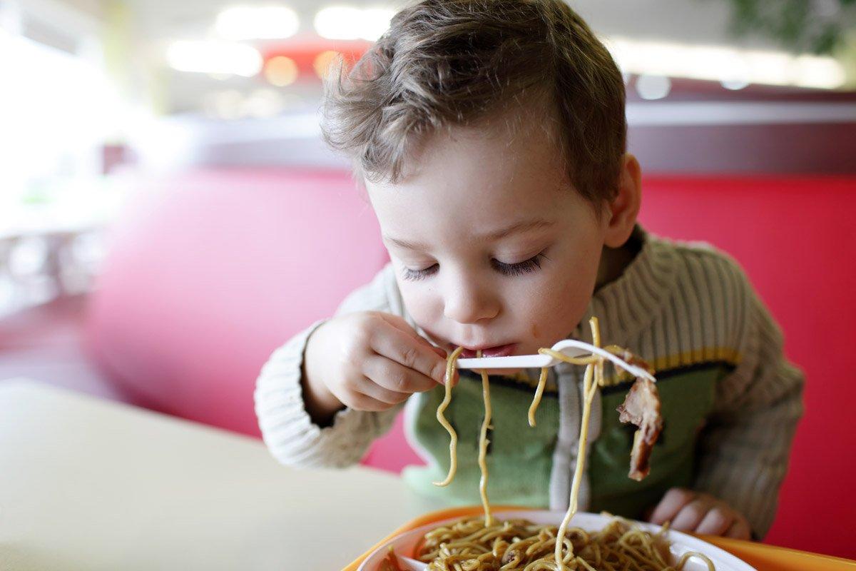 A little boy eats pasta.