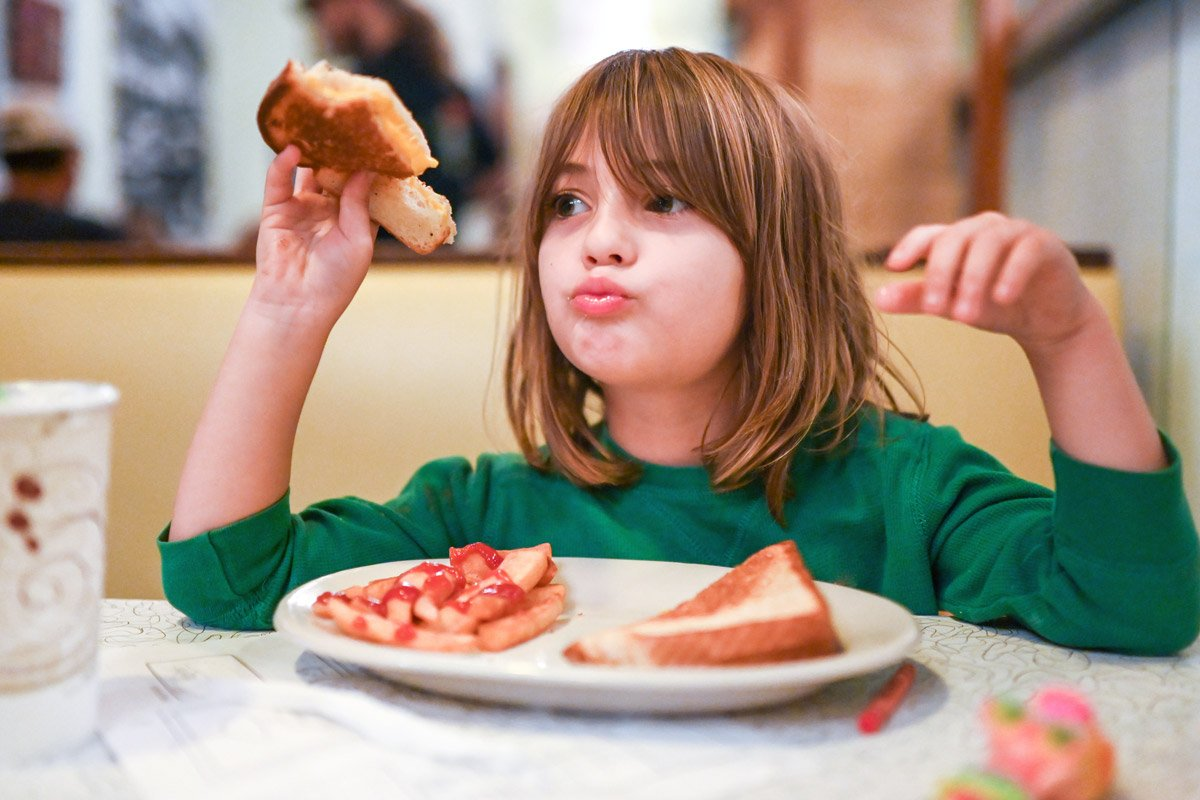 A little girl eats grilled cheese and fries.