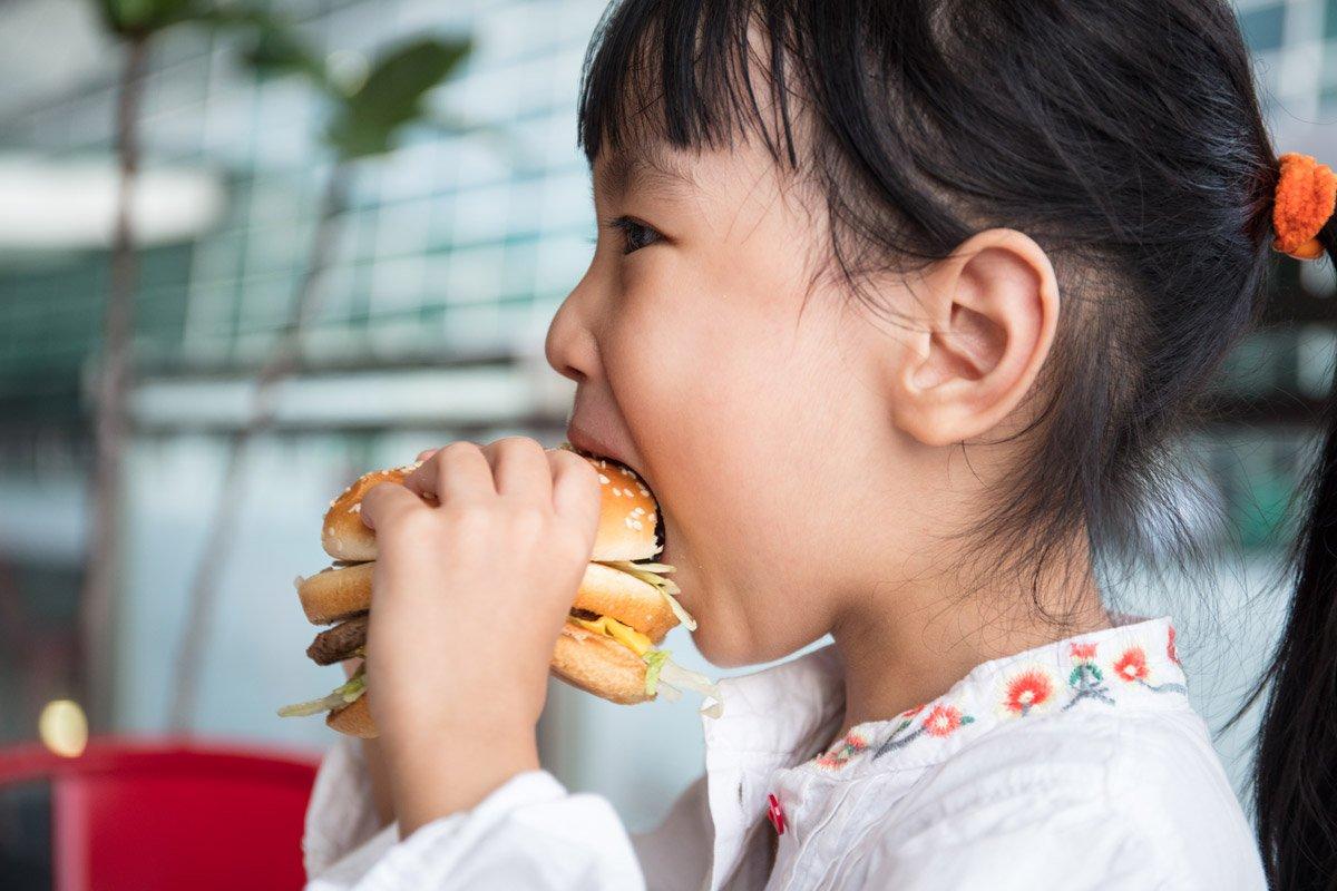 A little girl eats a burger.