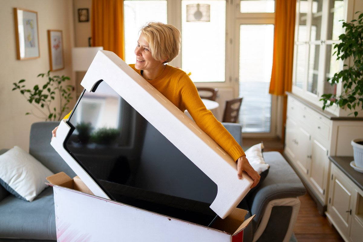 A woman opens up a box with a television in it.