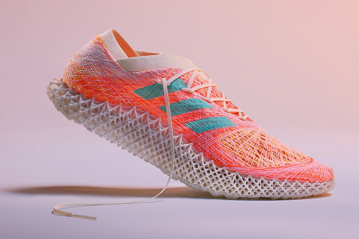 An Adidas shoe against a pink backdrop.