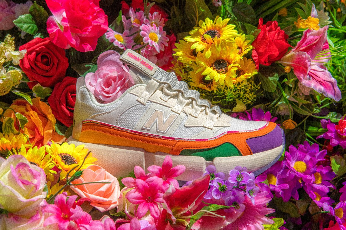 A new balance sneaker lays in a bed of flowers.