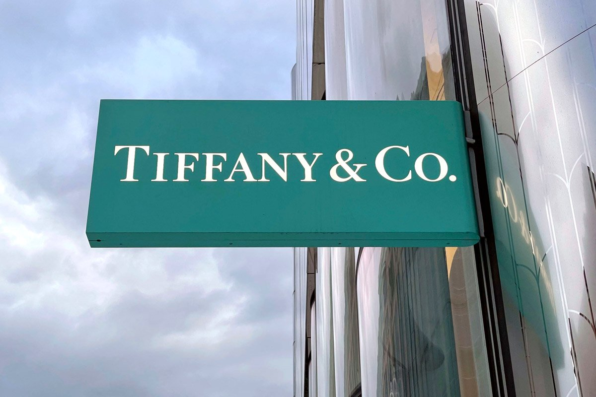 A Tiffany & Co sign hangs outside of the storefront against cloudy skies.
