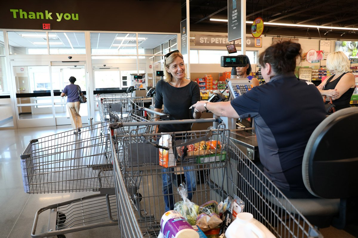 A person is checked out by a cashier at Aldi's.