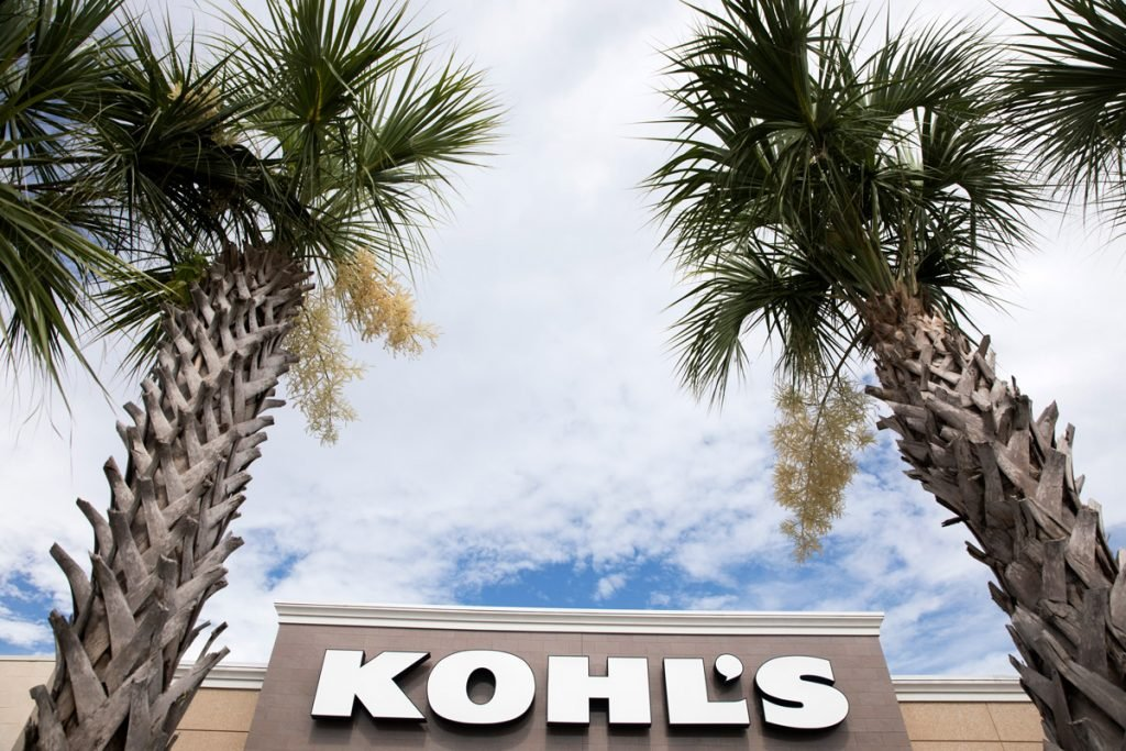 The outside of a Kohls store is shown with two palm trees near it.