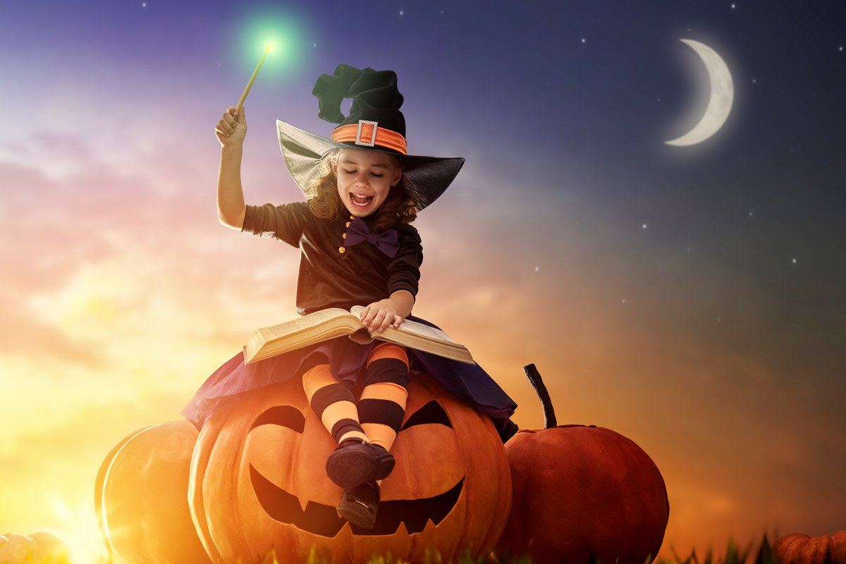 A little girl sits on top of a pumpkin while reading a book of spells.