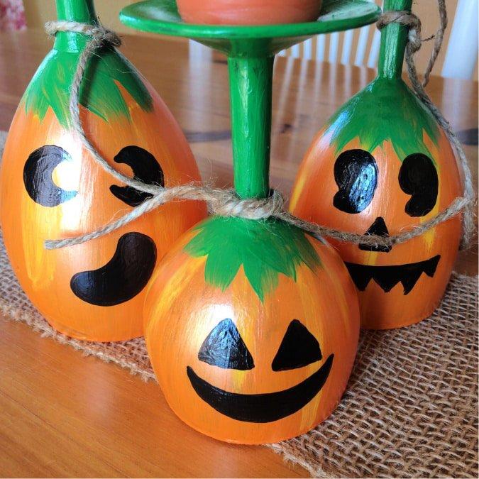 Pumpkins are spray painted on wine glasses.