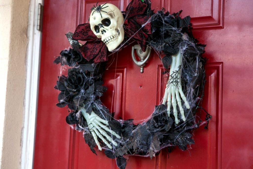 a DIY skeleton halloween wreath hanging on a red door