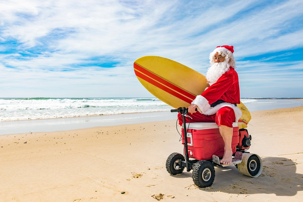 Santa Claus ride a scooter on the beach while holding a surf board.