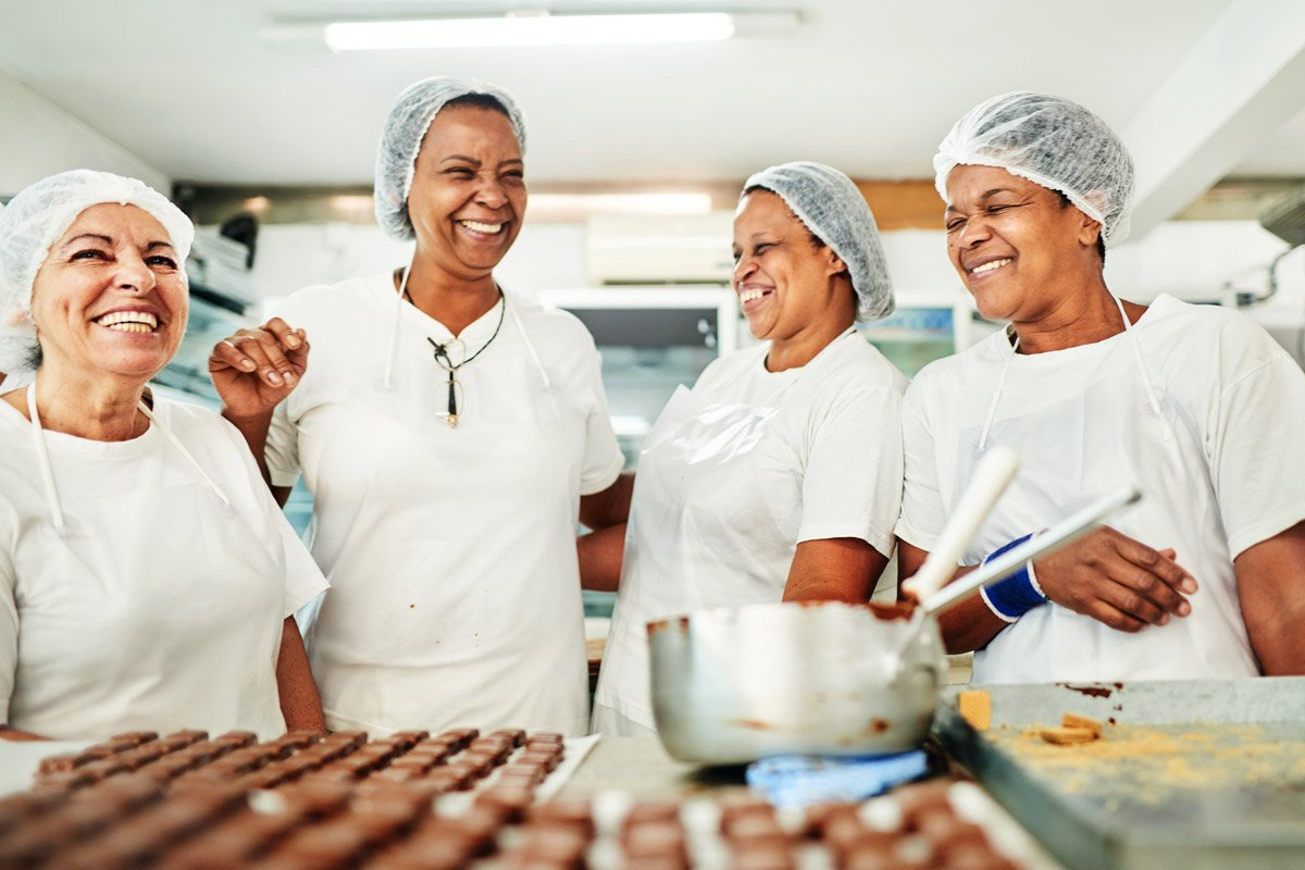 A group of women laugh as they bake desserts.